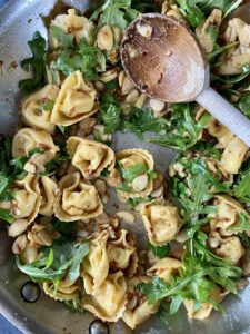 Mixing tortellini with almonds and arugula
